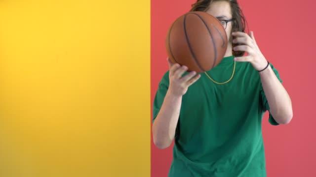 young man holding a basketball in front of colored wall - długie włosy filmów i materiałów b-roll