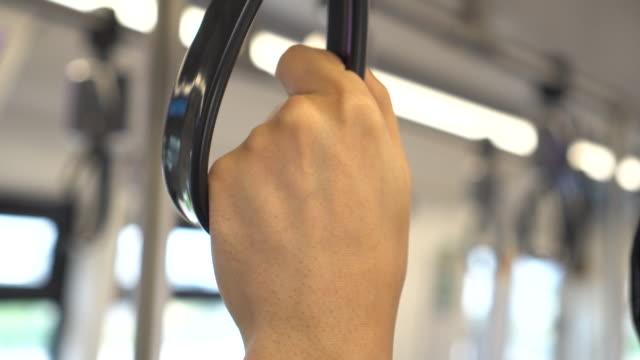 junger mann hält ein handlauf in einer u-bahn-zug in öffentlichen verkehrsmitteln. handriemen im fokus - turngerät mit holm stock-videos und b-roll-filmmaterial