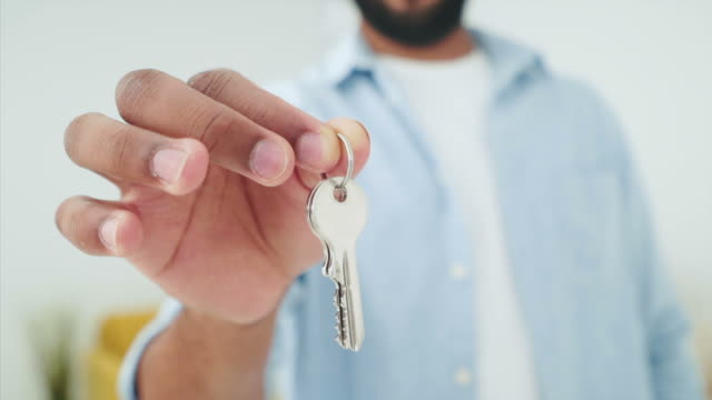 vídeos de stock e filmes b-roll de young man holding and showing home keys. - buy a house key