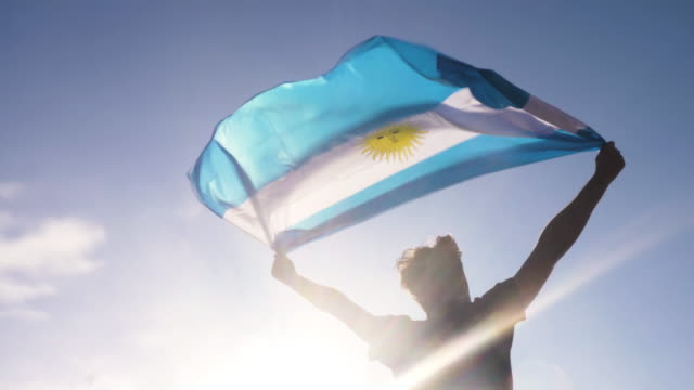 Young man holding argentinian national flag to the sky with two hands at the beach at sunset argentina video