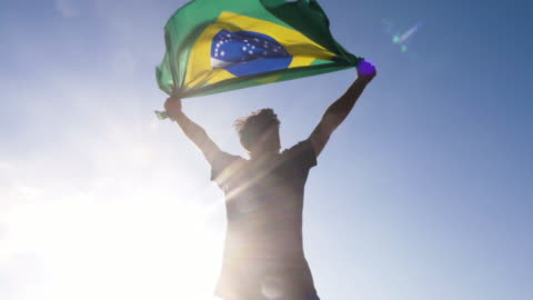 Young man holding brazilian national flag to the sky with two hands at the beach at sunset brazil Young man holding brazilian national flag to the sky with two hands at the beach at sunset flag stock videos & royalty-free footage