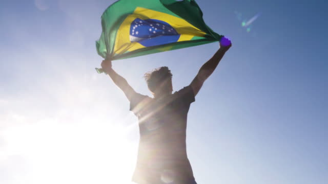 Young man holding brazilian national flag to the sky with two hands at the beach at sunset brazil Young man holding brazilian national flag to the sky with two hands at the beach at sunset brazil stock videos & royalty-free footage