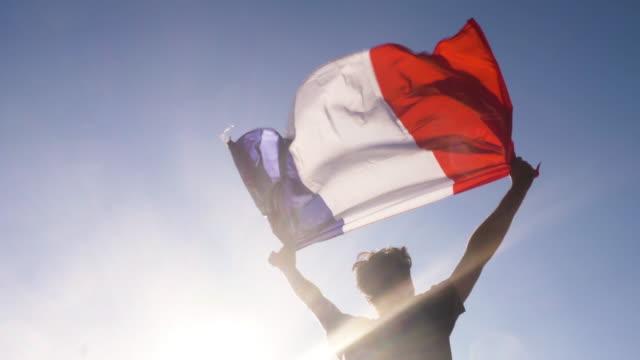 genç adam holding fransız gökyüzü günbatımı fransa sahilde iki elle için ulusal bayrak - fransa stok videoları ve detay görüntü çekimi