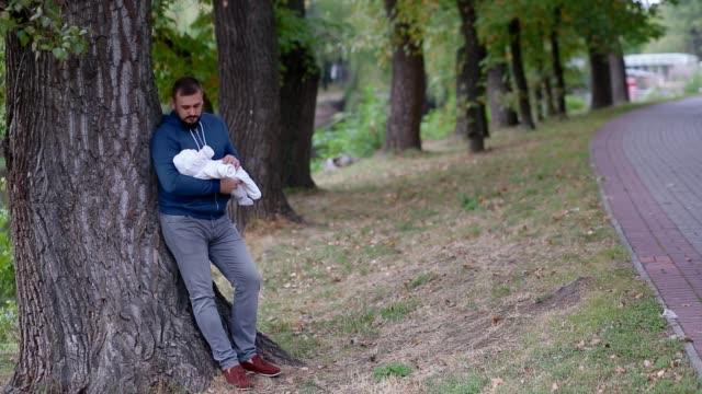 vídeos y material grabado en eventos de stock de joven sosteniendo a su hija recién nacida en sus manos - recién nacido 0 1 mes