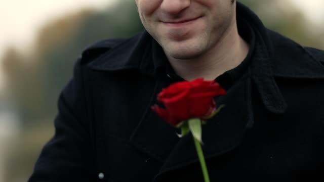 Hombre joven sosteniendo rosas rojas, lo que da un beso - vídeo