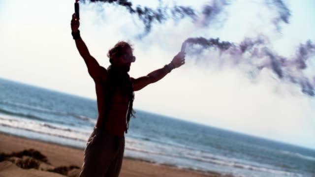 Young man holding smoke bombs at the beach video