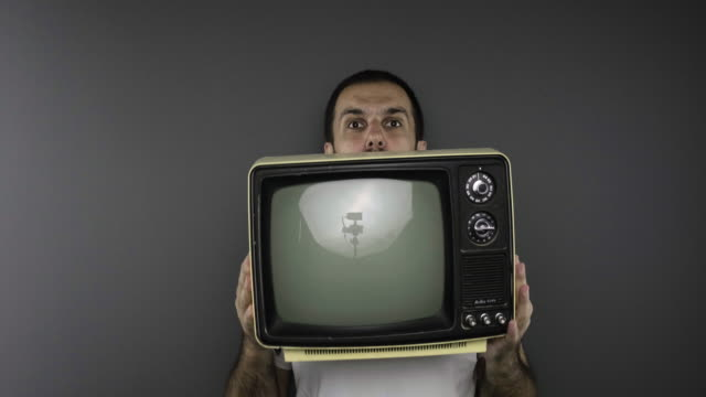 Young man holding vintage tv on gray background