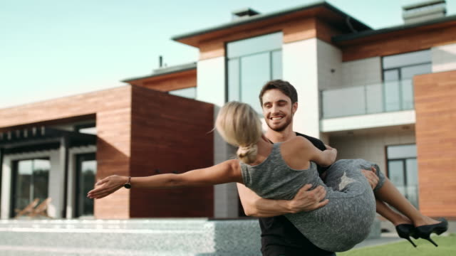 Young man holding woman near luxury house. Rich family hugging near new villa.