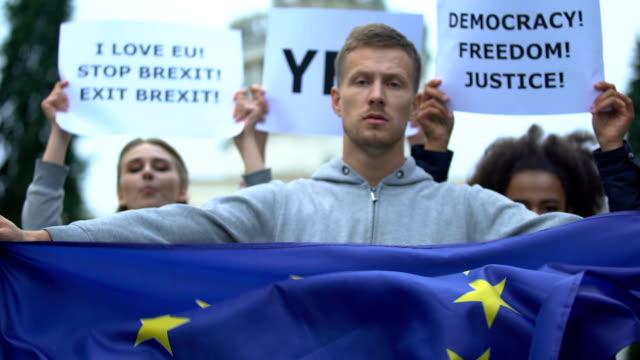 ung man innehar europeiska unionens flagga, aktivister med frihets slagord i bakgrunden - brexit bildbanksvideor och videomaterial från bakom kulisserna