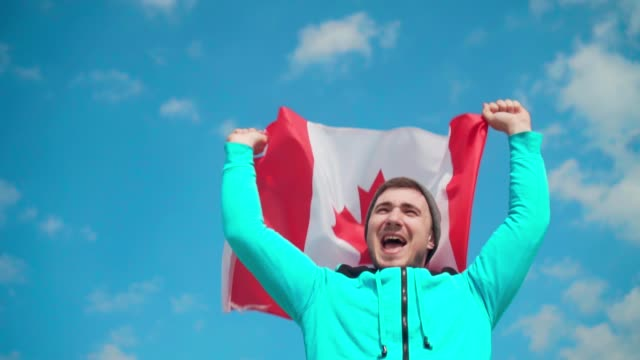 a young man in a blue sweater and hat holds the canadian flag in his hand. - canada day stock videos & royalty-free footage