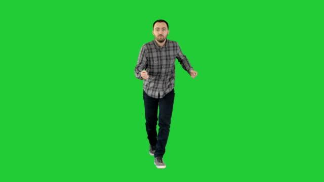 vídeos y material grabado en eventos de stock de hombre joven en un traje casual y bailando en una pantalla verde chroma key - moda playera