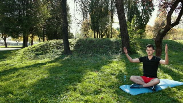 en ung man i en lotus position sittande på det gröna gräset i parken. begreppet lugn och meditation. händer i form av en pyramid. i en svart t-shirt och röda shorts på en blå matta. prores, slow motion - korslagda ben bildbanksvideor och videomaterial från bakom kulisserna