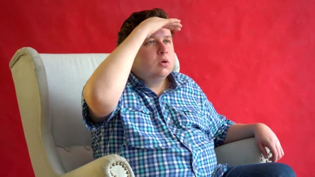 A young man in a plaid shirt looks into the distance with his hand to his face against red background video