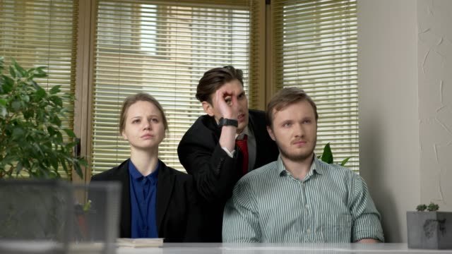 young man in a suit makes a presentation to two employees of the office. he tells the story impulsively, gestures with his hands. work in the office concept. 60 fps - sprzedawczyni filmów i materiałów b-roll