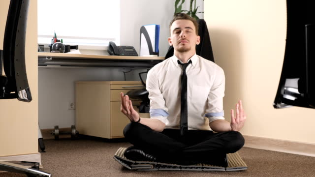 Young man in a suit meditating in a lotus pose in the middle of an office 60 fps Young man in a suit meditating in a lotus pose in the middle of an office 60 fps 4k meditating stock videos & royalty-free footage