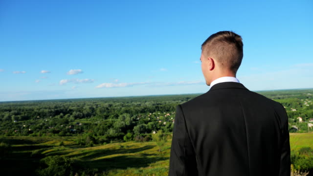 A Young Man In a Suit On Top of a Hill video