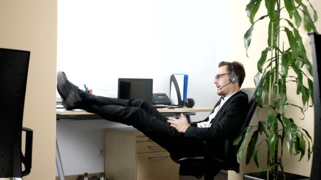 Young man in a suit sits on a chair in the office and talks on the headset 60 fps video