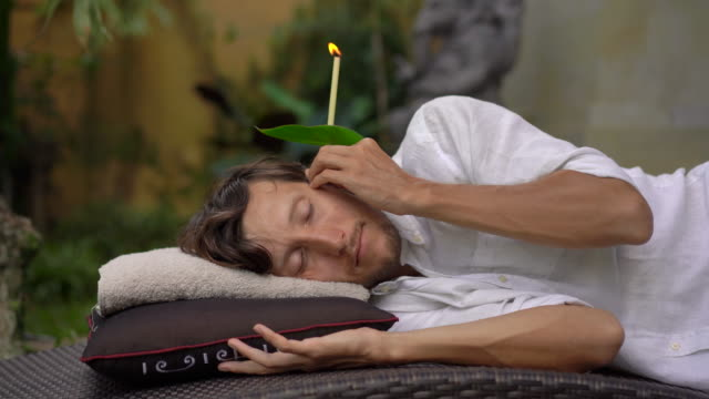 A young man in a tropical garden lays with an ear candle in his ear A young man in a tropical garden lays with an ear candle in his ear. indulgence stock videos & royalty-free footage