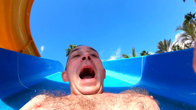 POV young man in a waterslide in water park in 4K Slow motion video