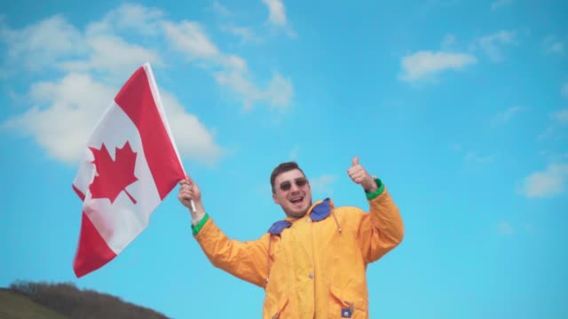 a young man in a yellow jacket, blue jeans and glasses is standing in the mountains, holding the flag of canada - canada day stock videos & royalty-free footage