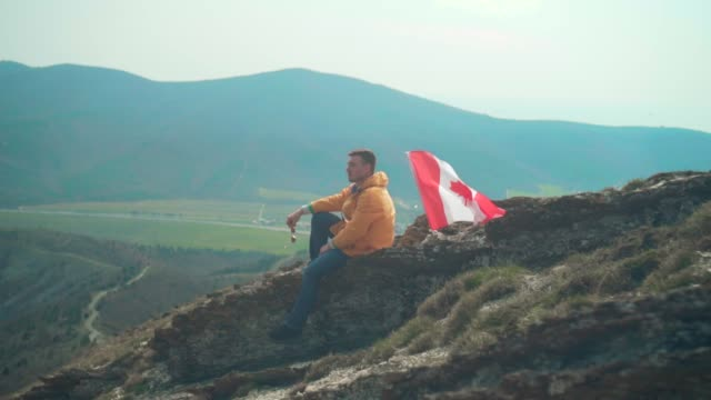 a young man in a yellow jacket, blue jeans and glasses sits on a ridge, followed by the flag of canada. - canada day stock videos & royalty-free footage