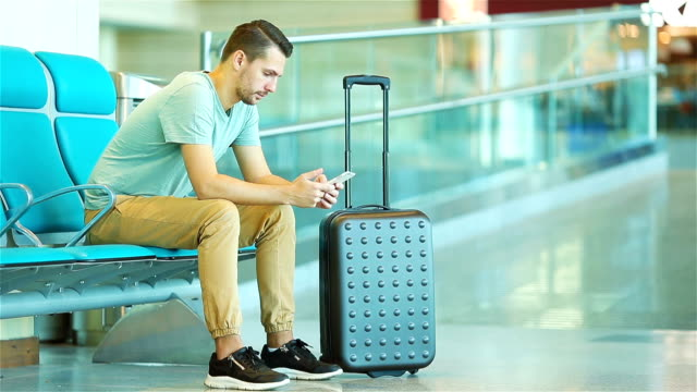 Young man in an airport lounge waiting for flight aircraft. Caucasian man with smartphone in the waiting room video