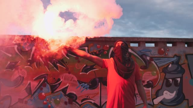 燃焼赤信号と目出し帽の若い男フレア落書き背景、スローモーションで屋根の上 - street graffiti点の映像素材/bロール