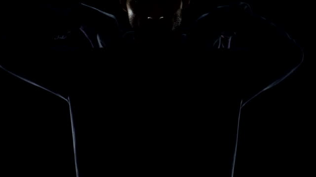 Young man in black hoodie invisible in night darkness, secret gangster closeup video