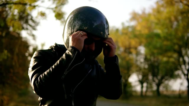 A young man in black leather jacket and helmet wearing sunglasses while sitting on his motorcycle preparing to start his journey in the forest. Slow motion shot A young man in black leather jacket and helmet wearing sunglasses while sitting on his motorcycle preparing to start his journey in the forest. Slow motion shot. crash helmet stock videos & royalty-free footage