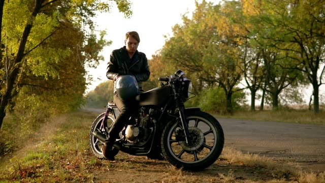 vídeos de stock e filmes b-roll de a young man in black leather jacket comes up to his motorcycle, sits there and puts a black helmet and sunglasses before starting his journey in the forest. slow motion shot - helmet motorbike