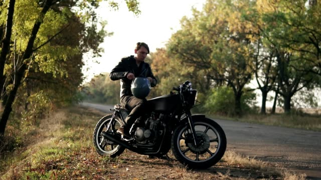 vídeos de stock e filmes b-roll de a young man in black leather jacket sits on his motorcycle and puts a black helmet to go on a journey in the forest. slow motion shot - helmet motorbike