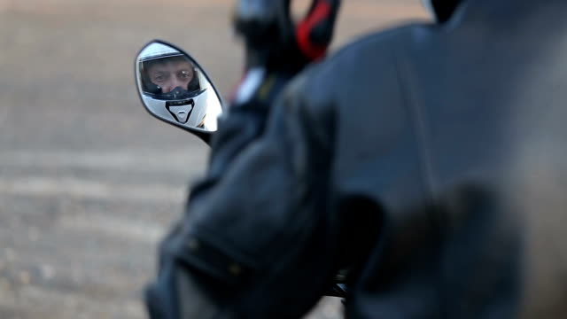 A young man in black leather jacket sits on motorcycle prepares his white helmet before journey at autumn sunset video
