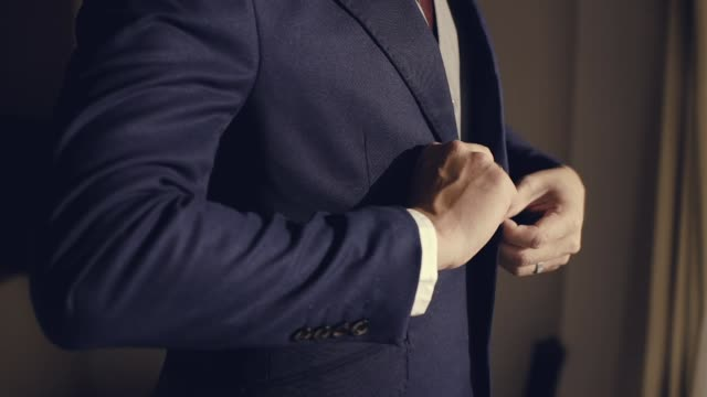 young man in black suit approaches a window. groom preparing for a wedding day. morning before ceremony - business suit stock videos & royalty-free footage