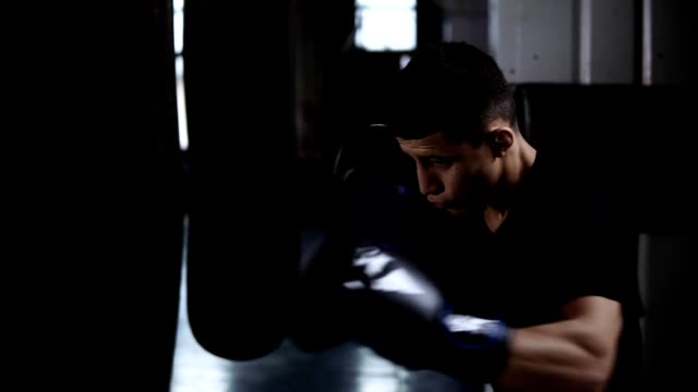 Young man in black T shirt fulfills the blows, exercising with big heavy boxing bag at gym. Strong punches, protecting face, block
