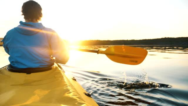 junger mann in blauer jacke paddelt ein kajak auf see bei sonnenuntergang, outdoor-aktivitäten aus nächster nähe - kanu stock-videos und b-roll-filmmaterial