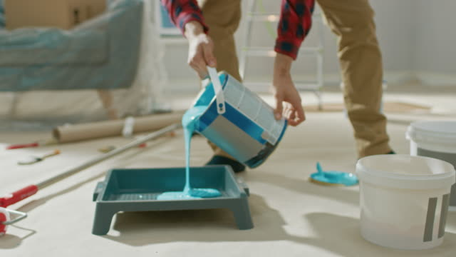 young man in brown jeans and red checked shirt picks up a can of light blue paint and pours it into a tray. room renovations at home. - muro video stock e b–roll