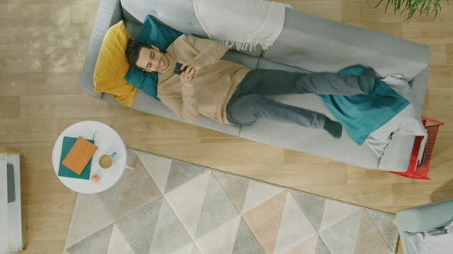 young man in brown jumper and grey jeans comes and lies down on a sofa, using a smartphone. he is happy and smiles. cozy living room with modern interior with plants and wooden floor. top view with zoom out. - kompozycja flat lay filmów i materiałów b-roll