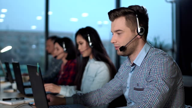 Young man in call center Young handsome men in checked shirt and headset working in call center in modern worldwide office he talking and looking on screen of desktop computer call centre videos stock videos & royalty-free footage
