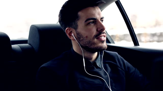 Young man in car listening music video