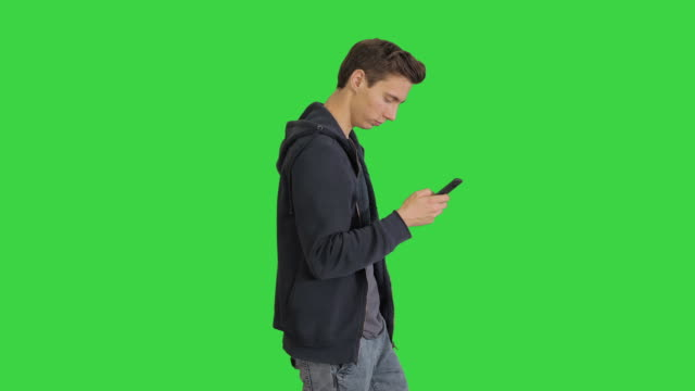 young man in casual clothes walking and texting on cell phone while walking on a green screen, chroma key - ludzka osada filmów i materiałów b-roll