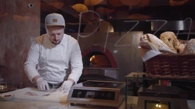 Young man in chef uniform cutting raw fish on cutting board.