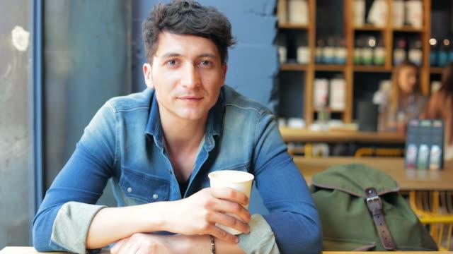 若い男性のコーヒーショップカメラを見ているます。 - カフェ文化点の映像素材/bロール
