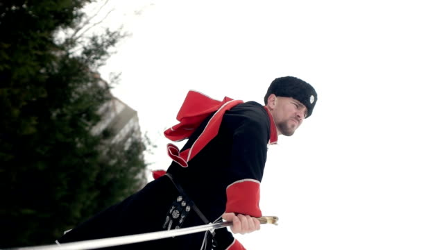 a young man in cossack clothes swinging a sword in a winter landscape in the snow. - nazionalità russa video stock e b–roll
