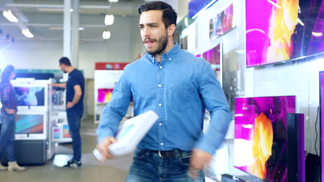 young man in electronics store purchased latest model of the tablet computer and dances happily with the box. bright and modern store has all the latest devices in store. - euforia video stock e b–roll