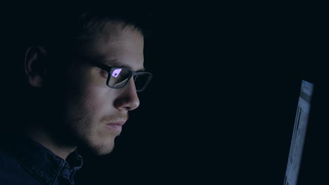 ung man i glasögon arbetar på laptop på natten i mörka kontor. designern fungerar på senare tid. - male eyes bildbanksvideor och videomaterial från bakom kulisserna