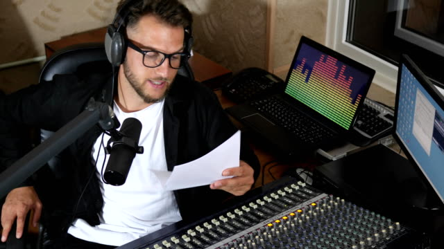 young man in glasses and headphones reads text into microphone while working on radio video