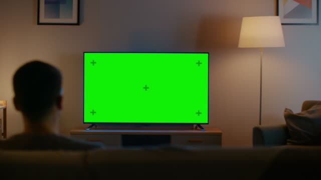 Young Man in Glasses is Sitting on a Sofa and Watching TV with Horizontal Green Screen Mock Up. It's Evening and Room at Home Has Working Lamps.