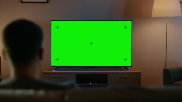 junger mann in gläsern sitzt auf einem sofa und watching tv mit horizontal green screen mock up it es evening and room at home has working lampes. - tv stock-videos und b-roll-filmmaterial