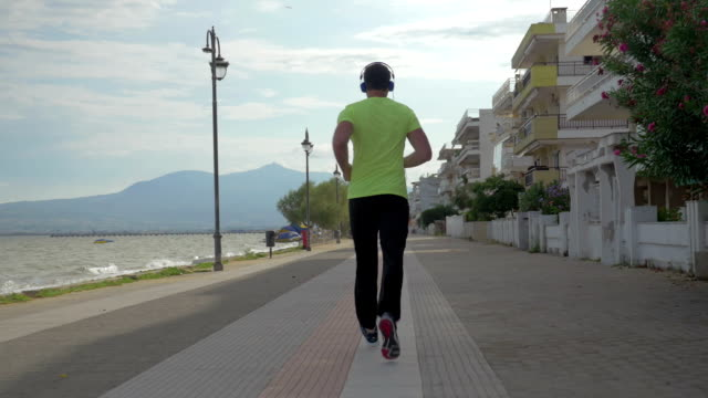 Young man in headphones runs on road of city Perea, Greece video