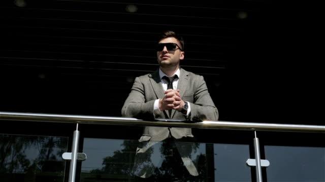 stockvideo's en b-roll-footage met jonge man in de jas en zonnebrillen zijn leunt op een leuning. - men blazer